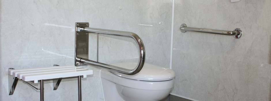 inside view of disabled shower room showing toilet, grab handles and wall seat