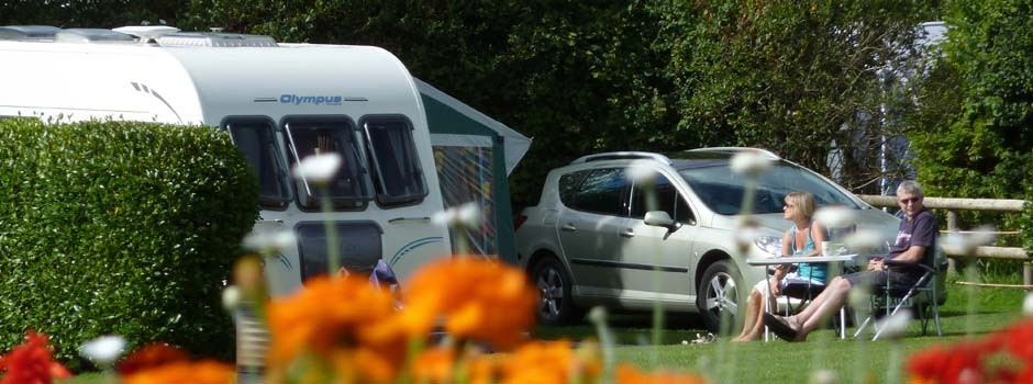 couple sat outside a caravan and awning on pitch 60 with orange flowers in foreground