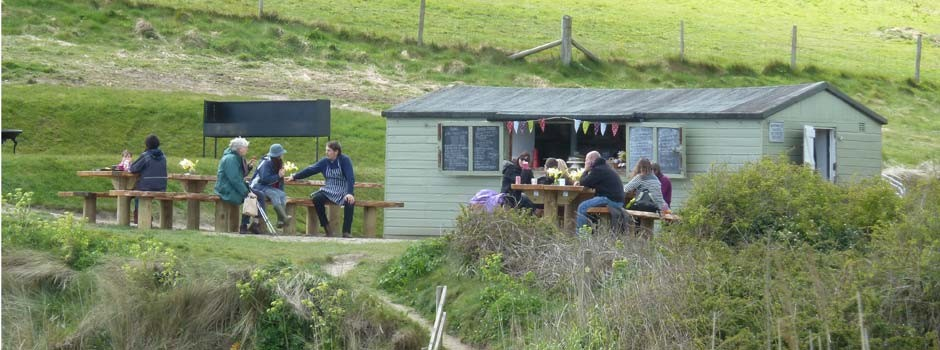 people sat outside the Hidden Hut at Porthcurnick beach, Portscatho