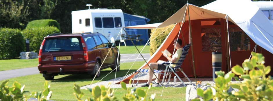 gentleman sat reading in the sunshine outside a tent on pitch 53