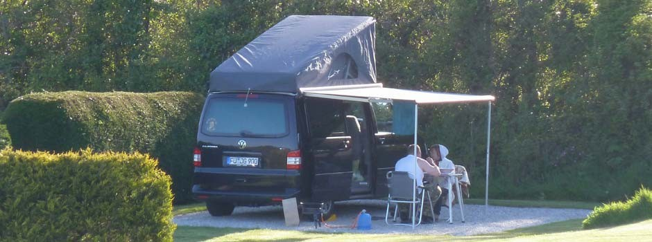 people sat eating outside a foreign campervan on pitch 22
