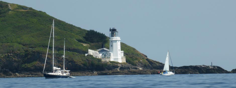 St Anthony's lighthouse from the water with boats sailing past in front