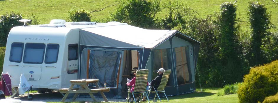 couple sat outside a caravan and awning on pitch 18