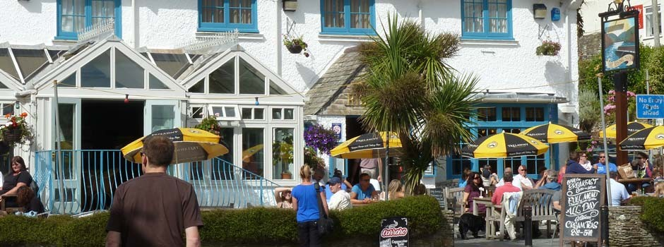 people sat at tables outside the Rising Sun pub in St Mawes