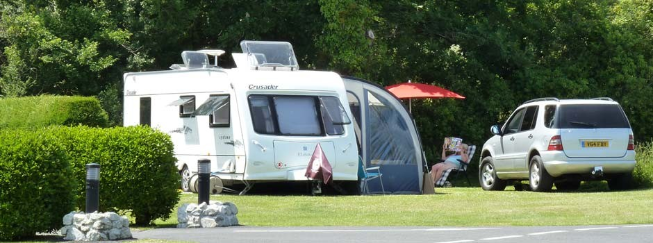 woman reading sat outside a caravan and awning on pitch 22