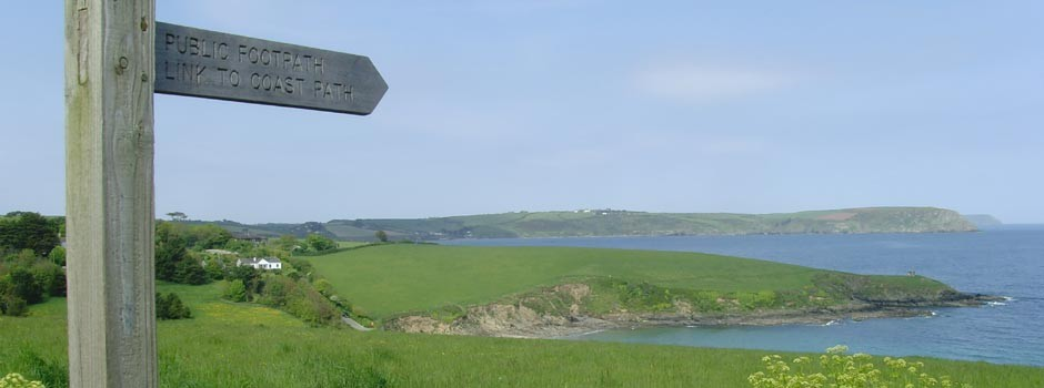 wooden signpost showing directions to coastal footpath at Portscatho