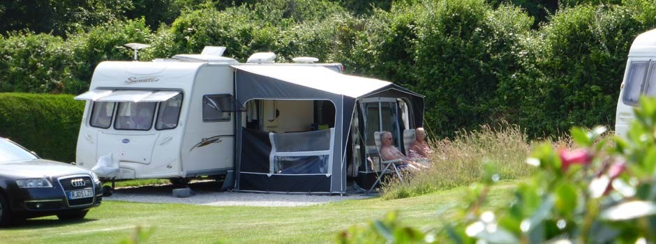 couple sat outside a caravan and awning on pitch 20