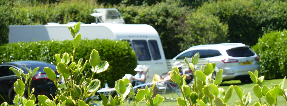 people in the sunshine sat outside a caravan on pitch 60