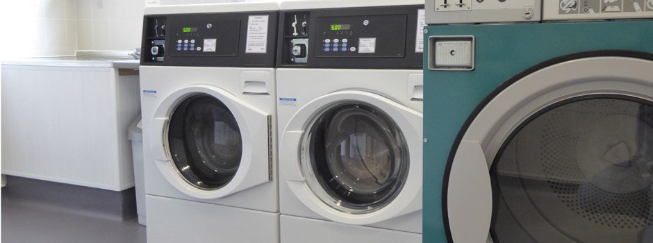 washing machines, tumble dryers and sink in the laundrette